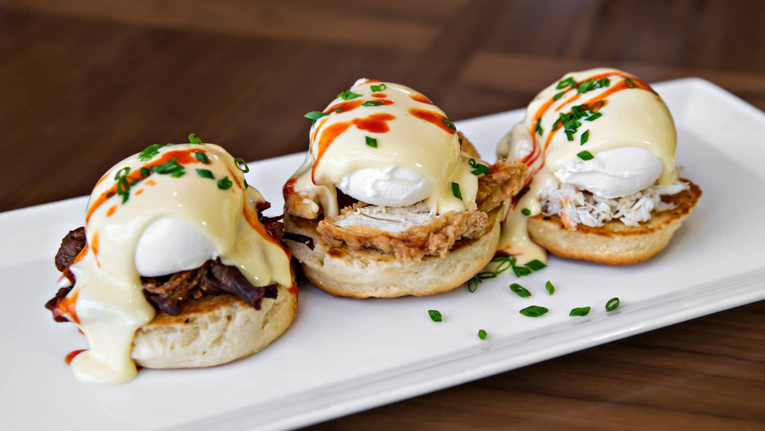 Law eggs Benedict, three English muffins topped with poached eggs, fried chicken, brisket, crab and hollandaise sauce