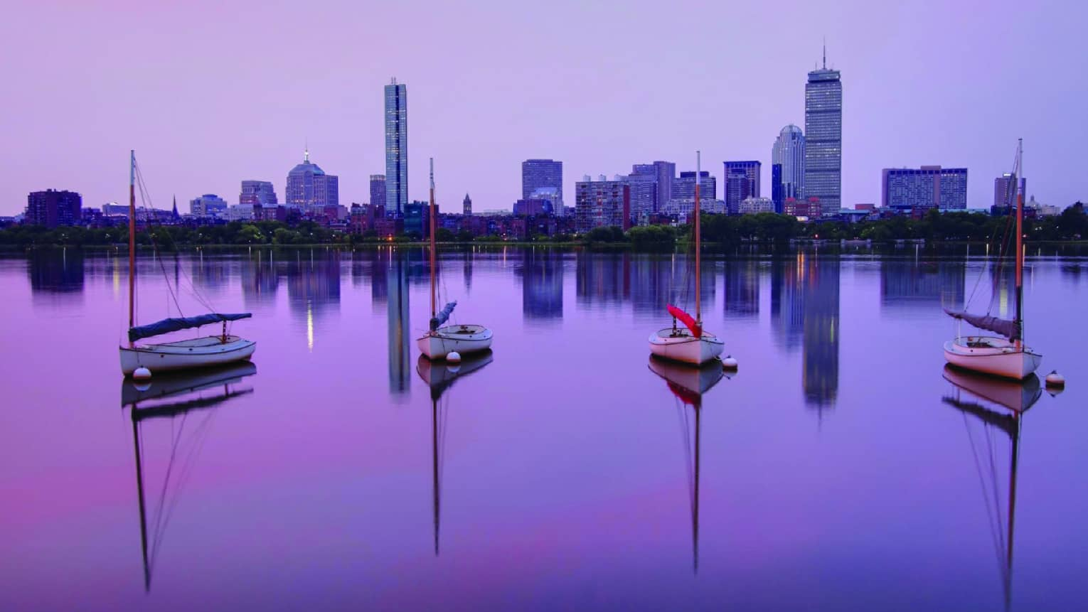 Sailboats parked on the Charles River, Boston skyline in background, purple sunrise