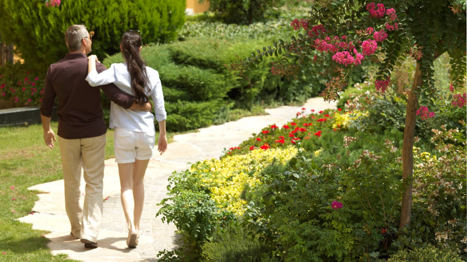 Back of man and woman walking with arms around each other through sunny garden