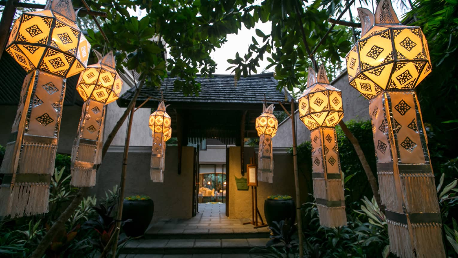 Long glowing Thai lanterns with fringes hang from trees along pavilion walkway