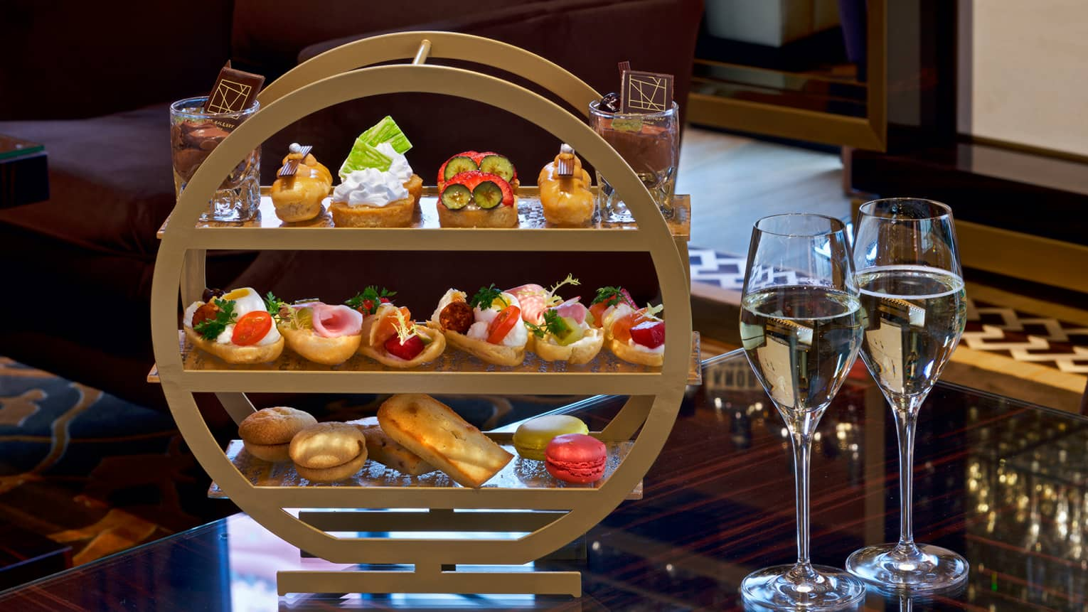 Afternoon tea three-tiered tray with selection of sandwiches and desserts, two glasses of white wine