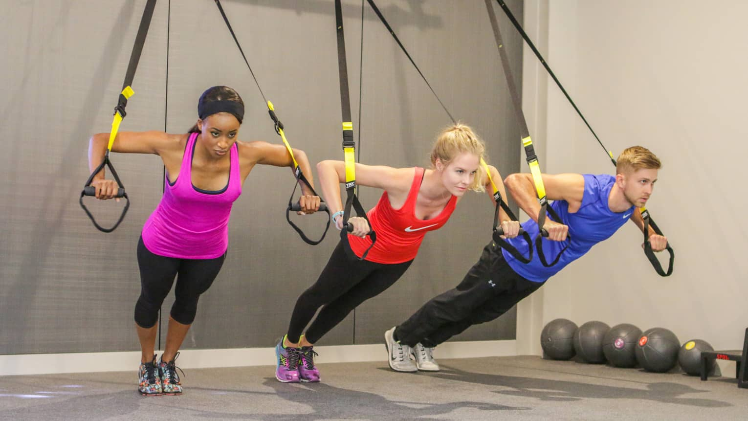 Three people in exercise clothes hold handles of pilates bands, hang forward in Fitness Centre