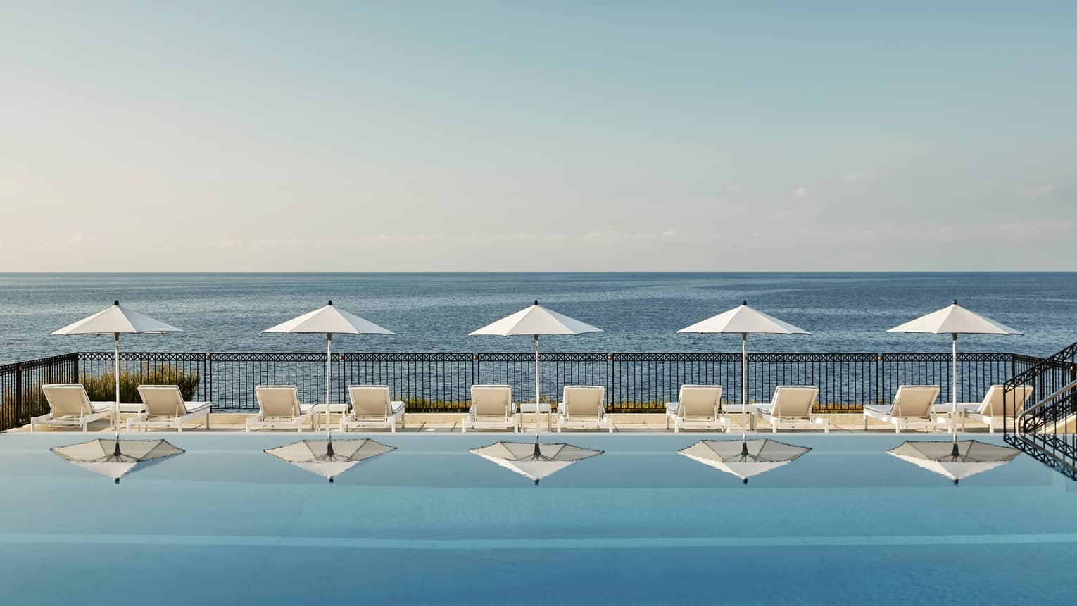 White patio chairs, umbrellas reflected on outdoor swimming pool by sea