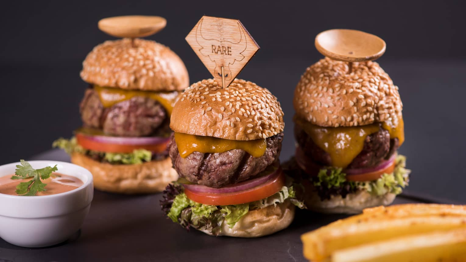"Three small beef cheeseburger sliders with lettuce and tomato, front one with wooden tag in bun reading ""rare"""