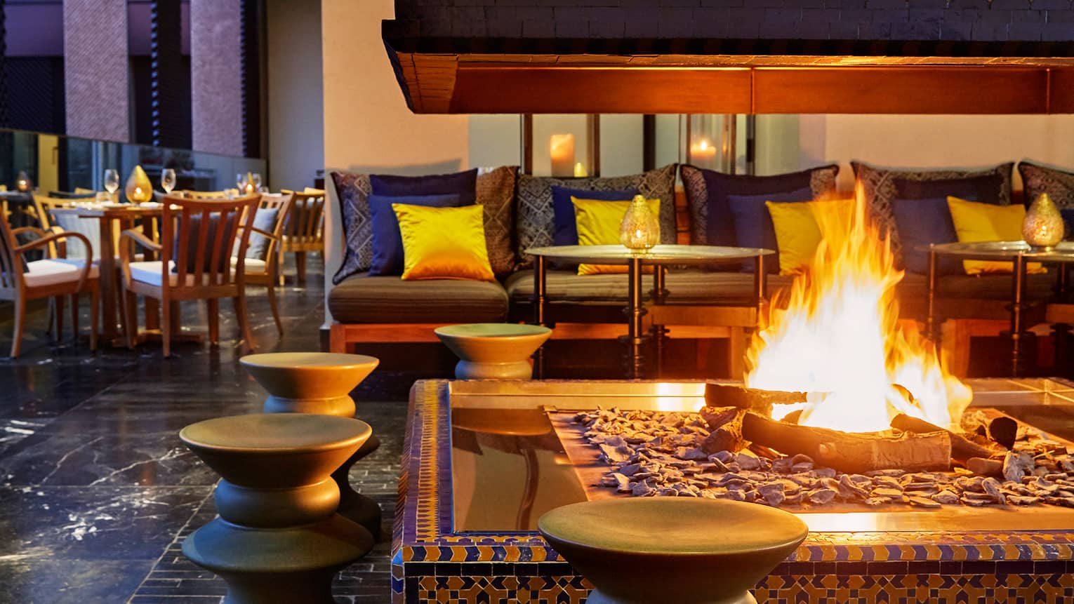 Outdoor fireplace in front of patio benches, pillows on Mint restaurant terrace