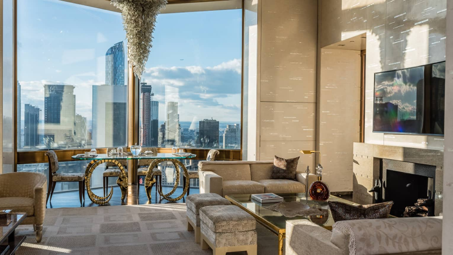 Bright Ty Warner Penthouse with modern gold dining table, chandelier by floor-to-ceiling window