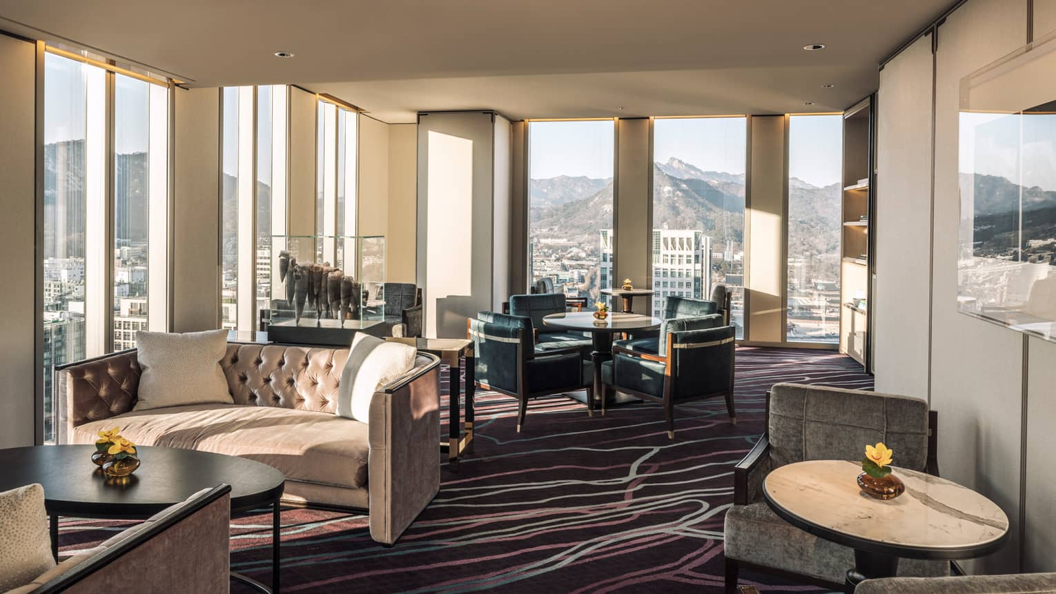 Lounge with tufted velvet sofas, cocktail tables and armchairs, floor-to-ceiling windows