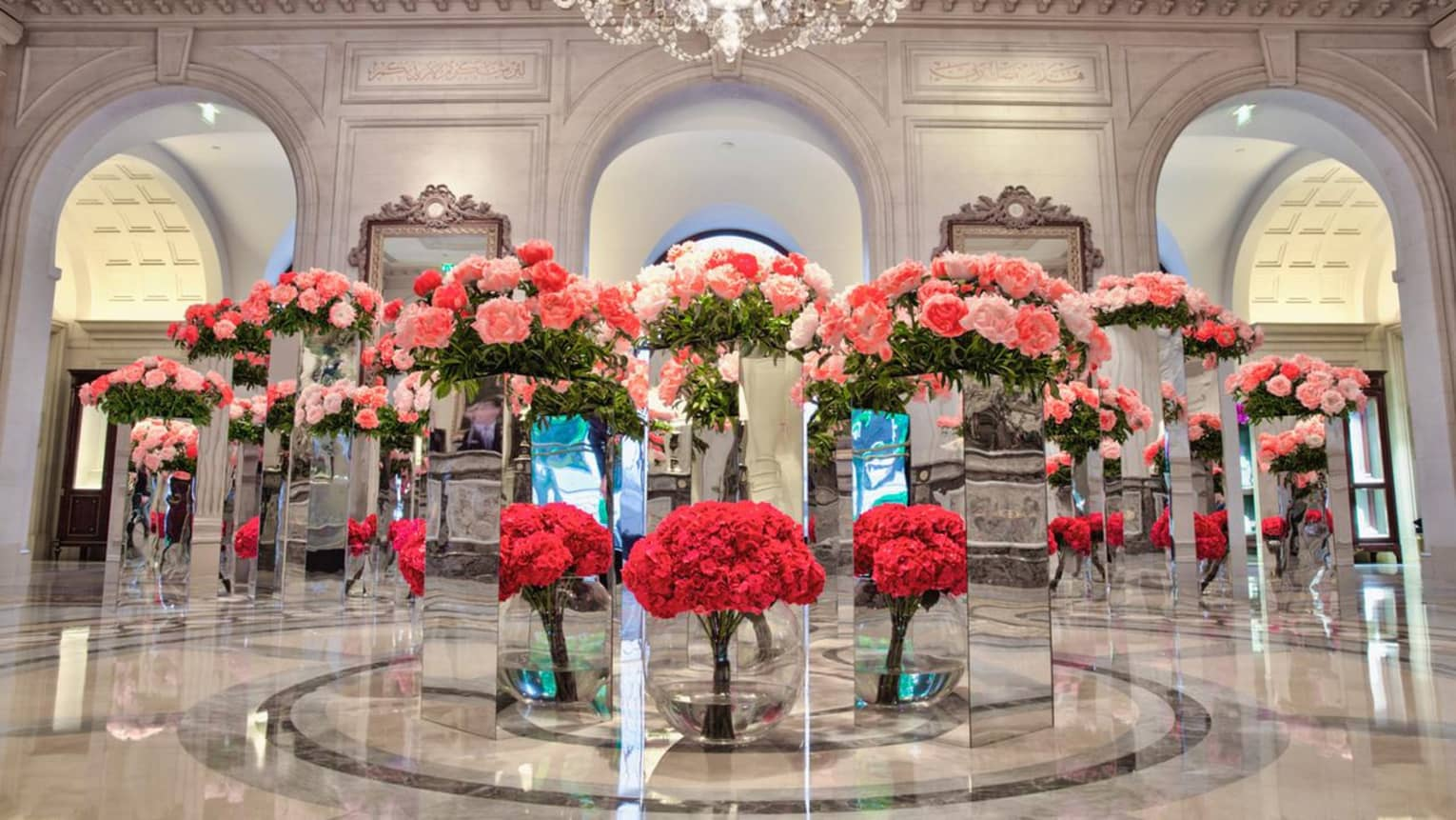 White marble lobby with multiple glass podiums with red and pink flower arrangements