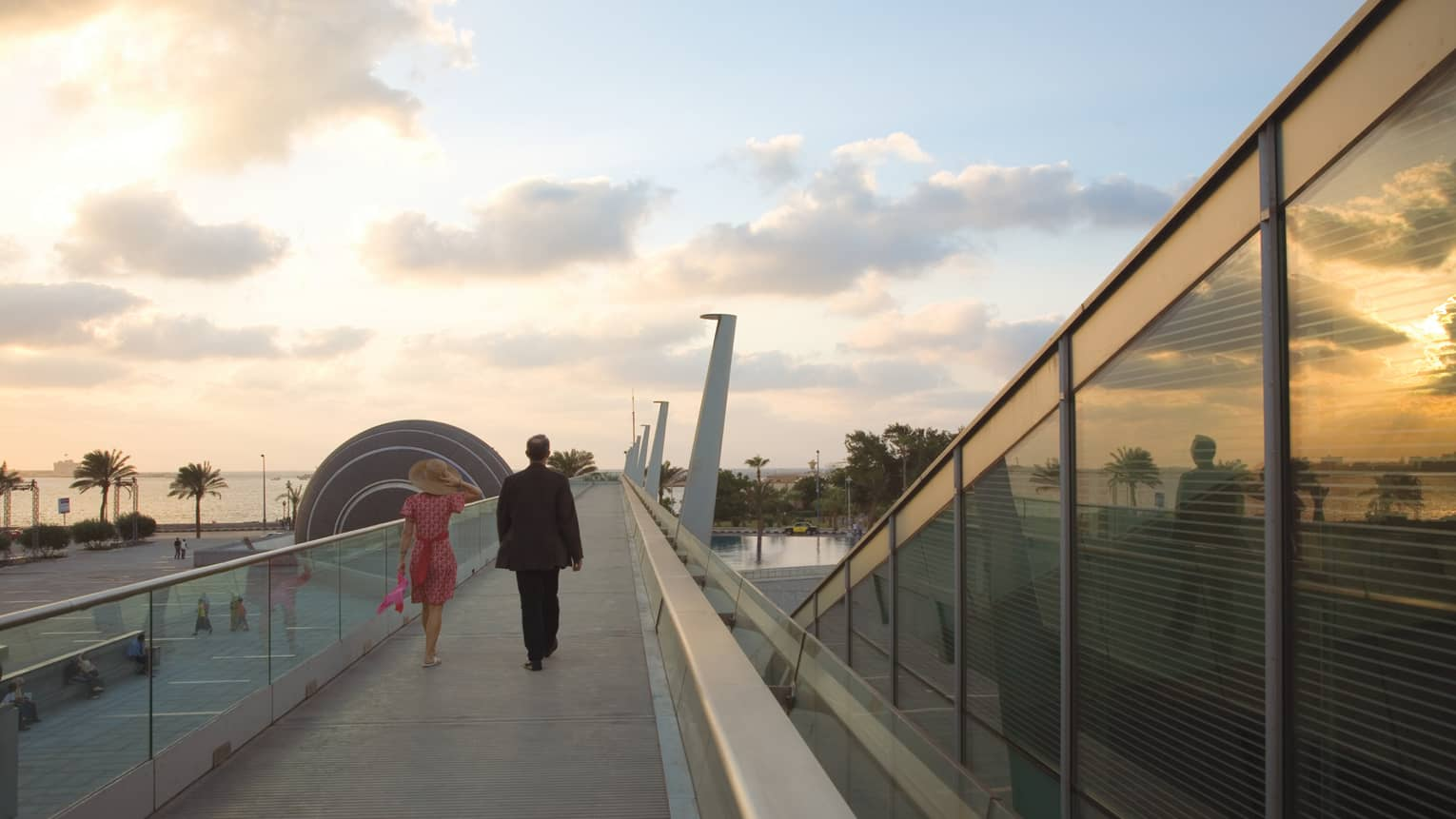 Back view of man in suit and woman in dress walking along raised Bibliotheca Alexandrina walkway at sunset