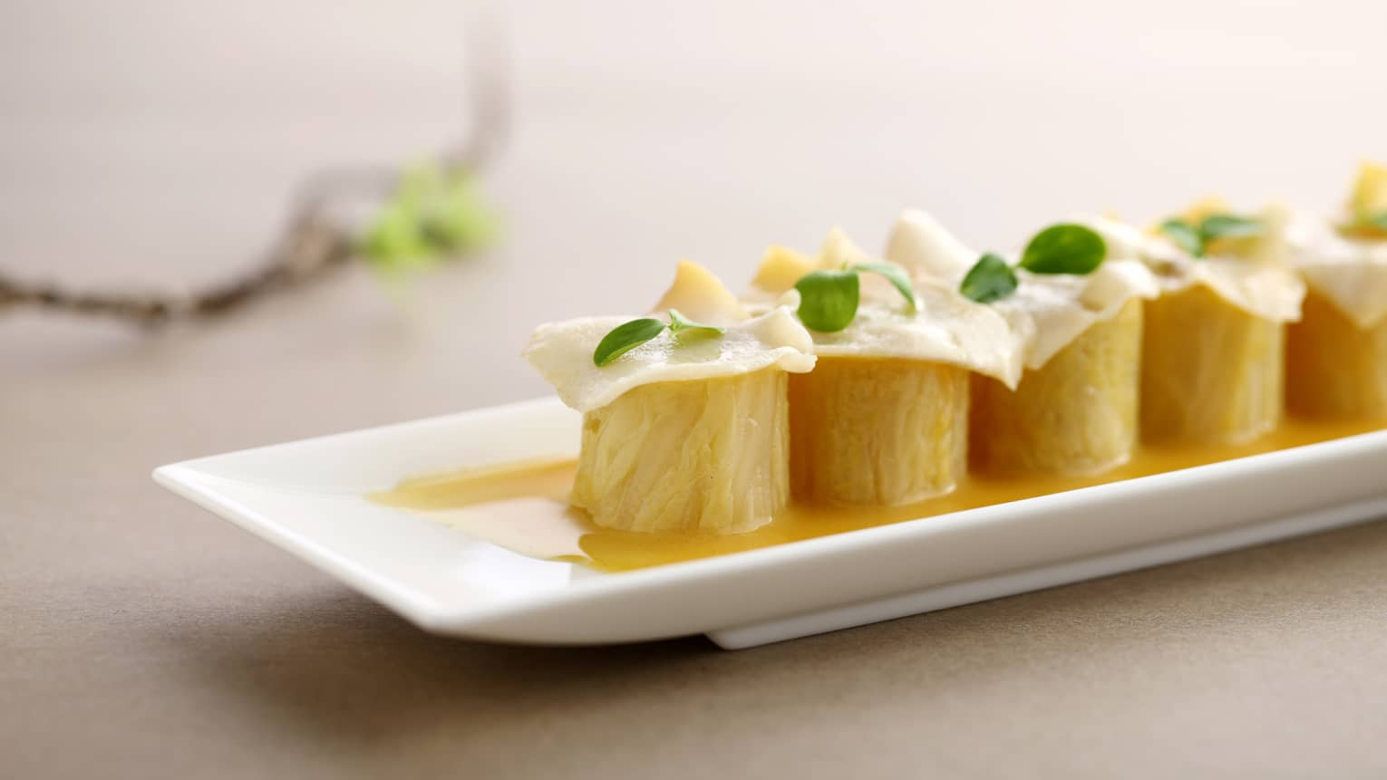 Beijing-Style, Yellow-Mustard Cabbage Rolls in rows on long white ceramic platter
