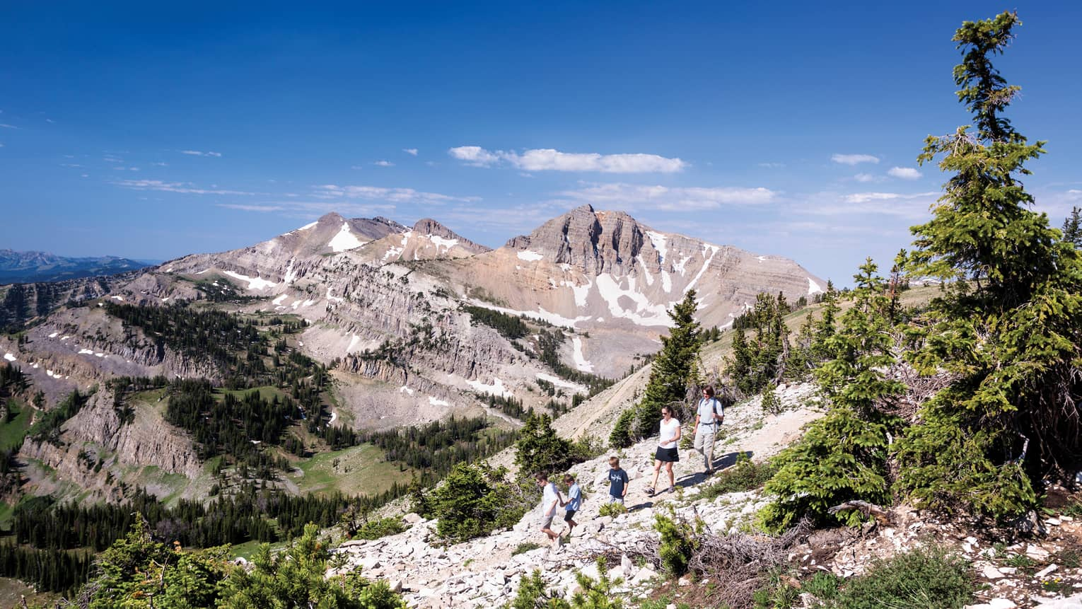 Family hikes along rocky path on mountain, sweeping views of mountain range