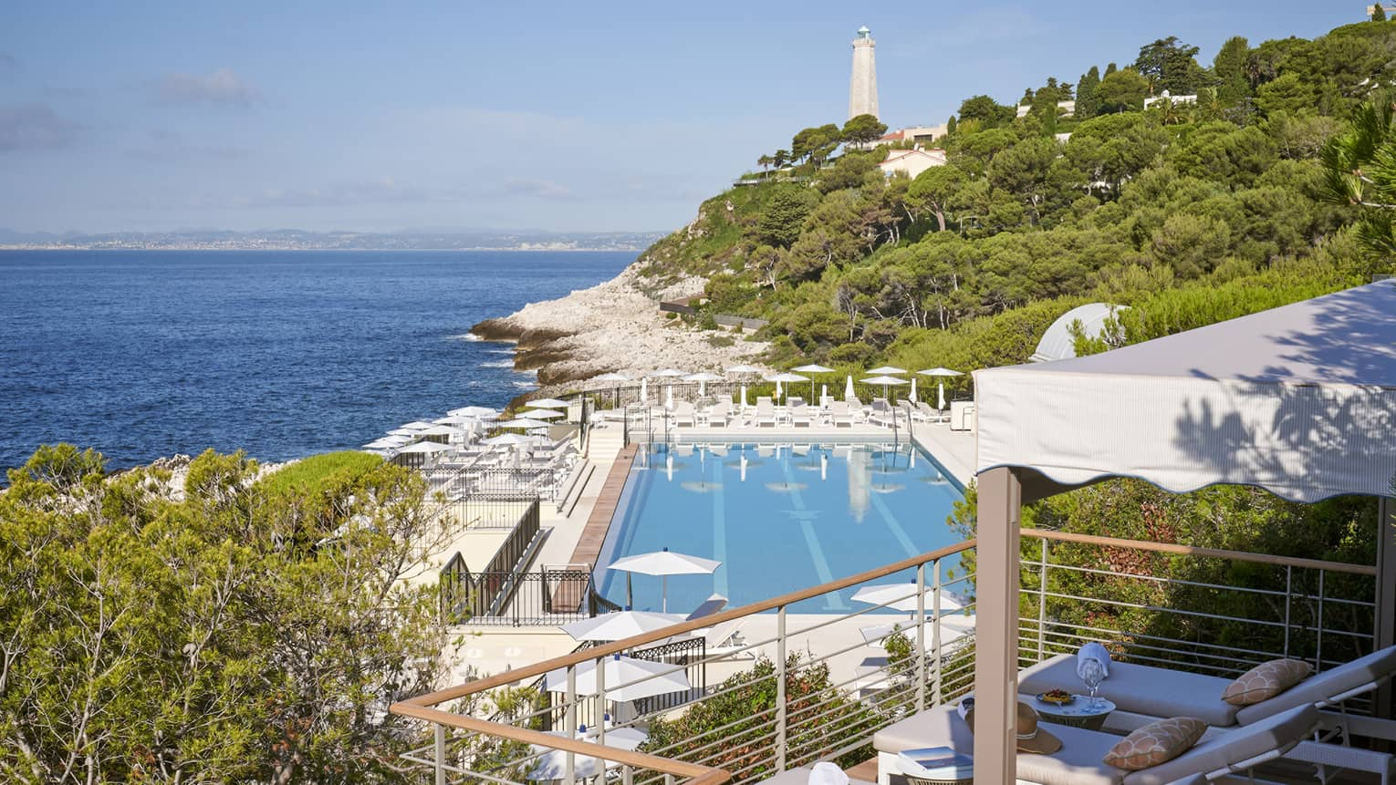 View from terrace of Club Dauphin pool, Mediterranean, green hillside and lighthouse