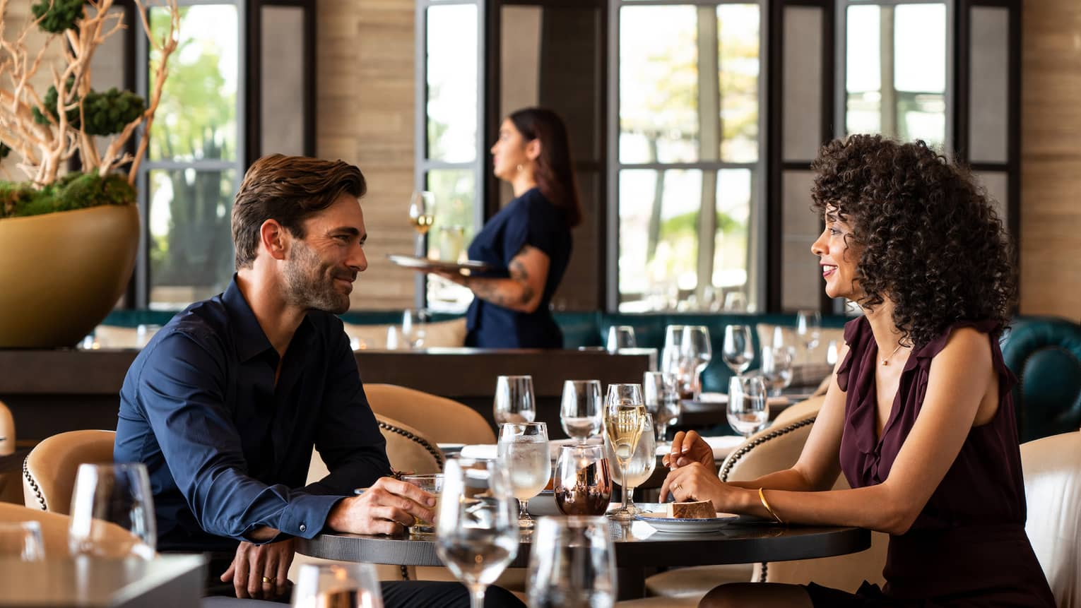 A man and woman enjoy a date at trendy cinderhouse – furnished with black square tables, camel leather colored chairs, and modern sconce lighting