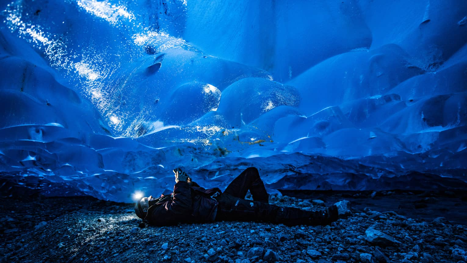 Man lies on back on rocky ground, headlamp shines up on thick ice cap with blue hues
