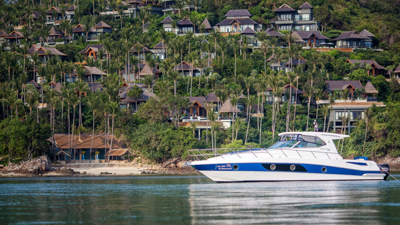 White and blue private fishing boat on ocean in front of mountain dotted with resort villas