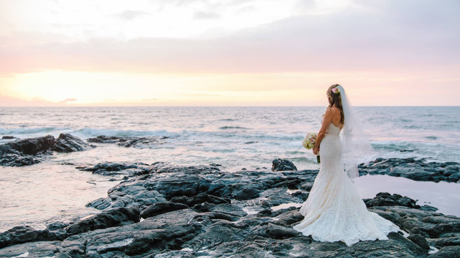 Bride in white wedding gown poses on black lava rocks by ocean