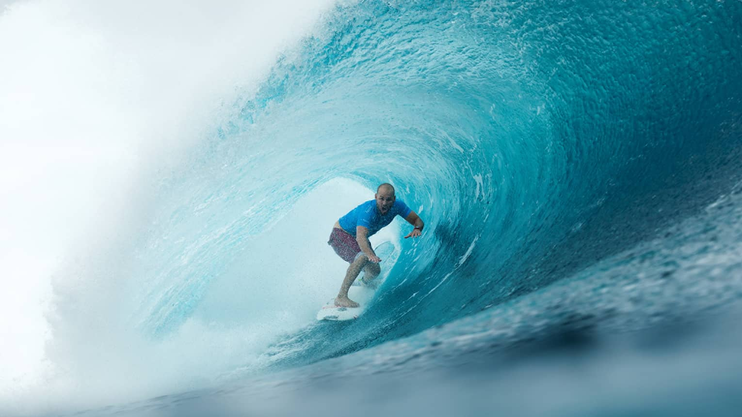 Man on surfboard surfs along large waves in remote Outer Atolls