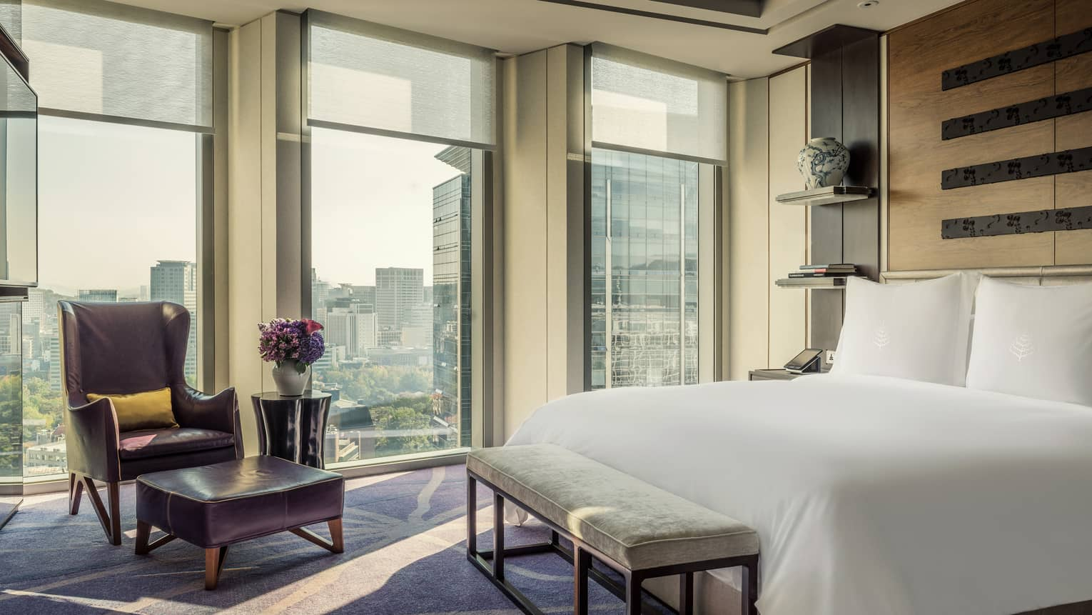 Sejong Two-Bedroom Suite bed with bench at foot, leather wingback armchair and ottoman by window with Sejong Road views
