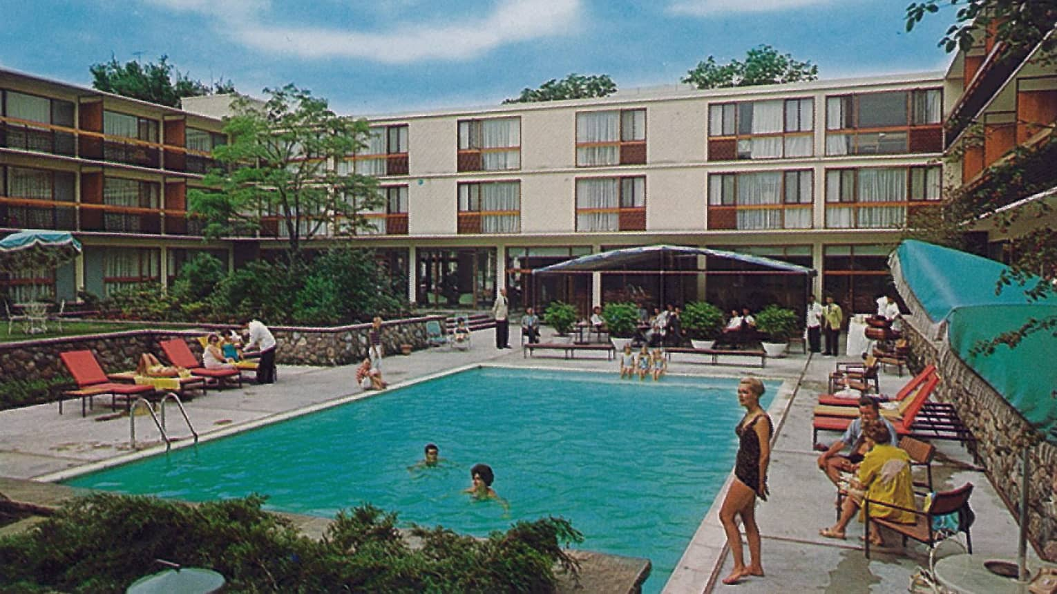 Historic 1960s photo of guests enjoying outdoor swimming pool, deck at Four Seasons Hotel
