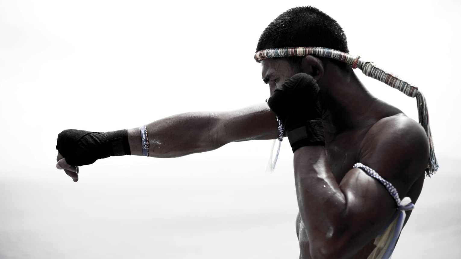 Muay Thai boxer punching, silhouetted by a white-grey background