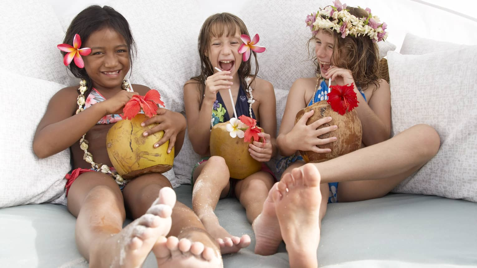Three young girls laughing with tropical drinks, tropical flowers in their hair