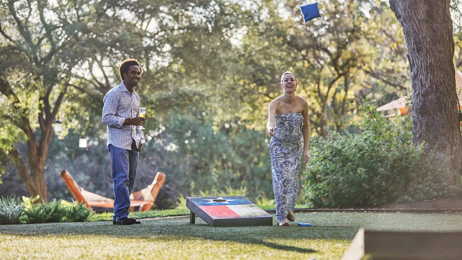 Laughing woman tosses bean bag on lawn, man holding beer watches