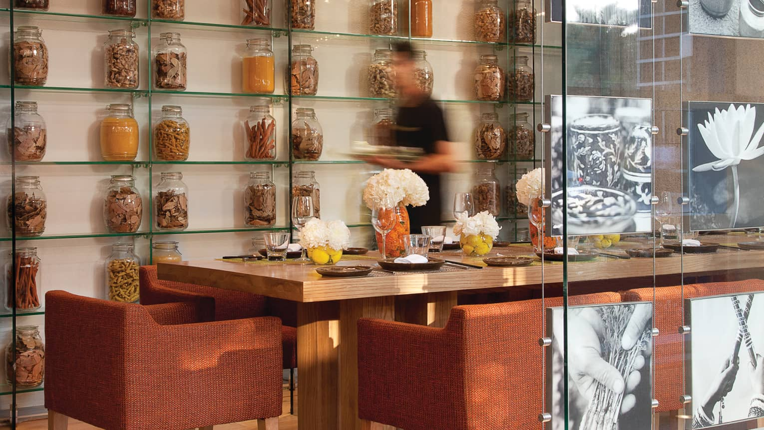 Blurry image of server walking quickly past table, wall with large glass spice jars