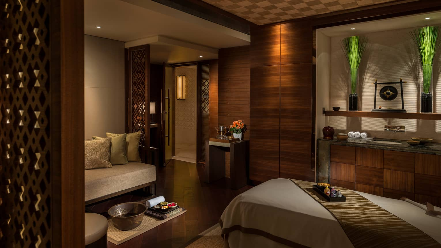Spa treatment room with carved wood detail walls, bed and table with trays with oils