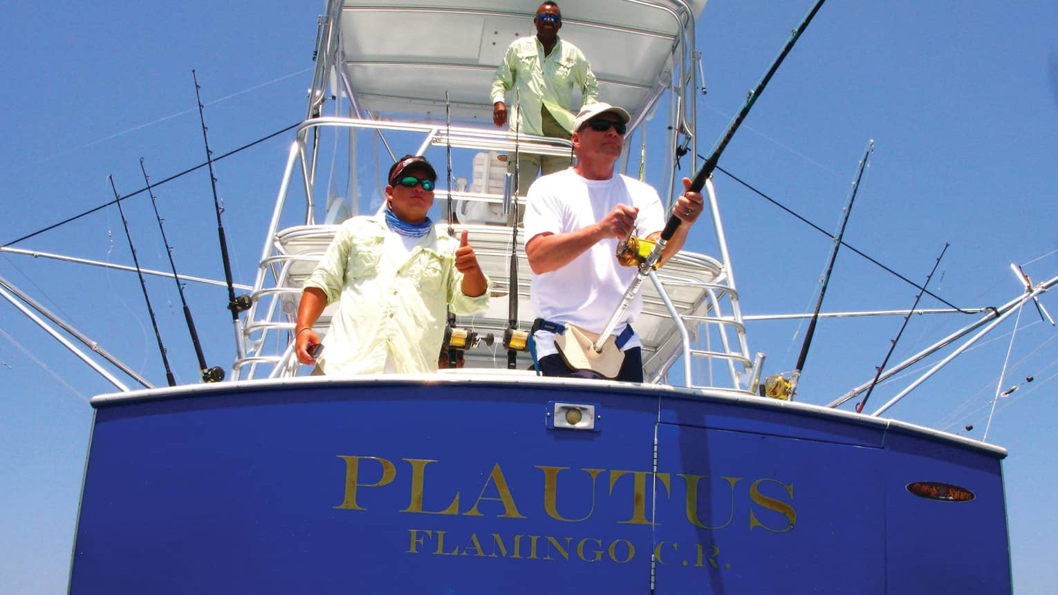 Three men with fishing rods at front of deep-sea fishing boat on sunny day