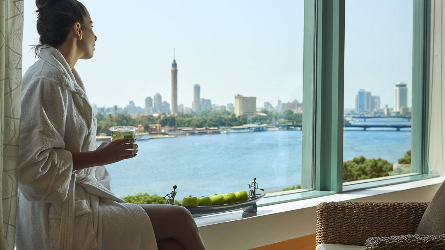 Woman wearing white robe sits on window ledge overlooking Nile River