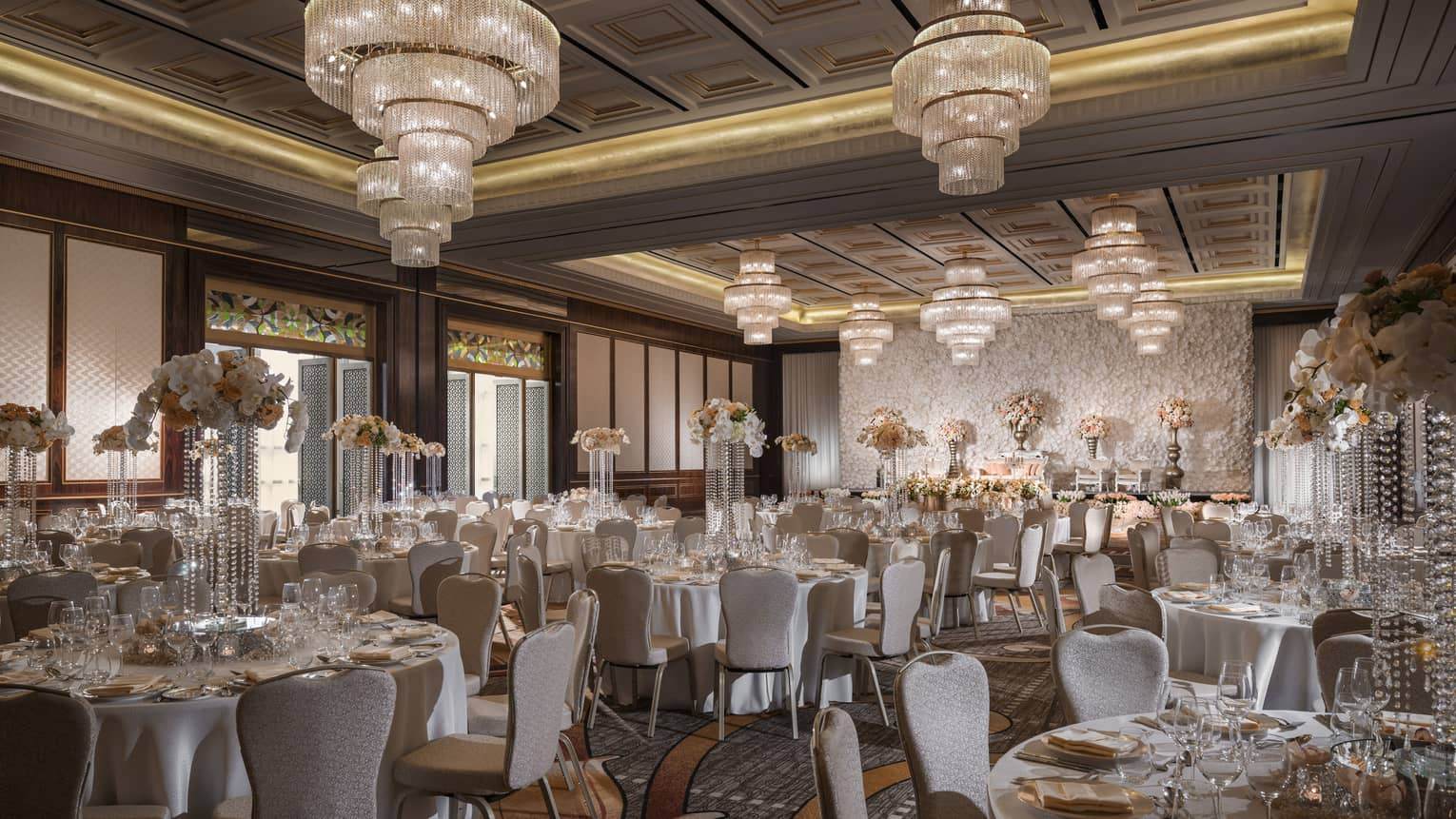 Large crystal chandeliers hang over round banquet tables in ballroom