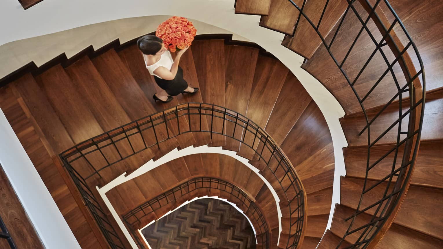 Aerial view of woman holding pink rose flower arrangement walking down wood spiral staircase
