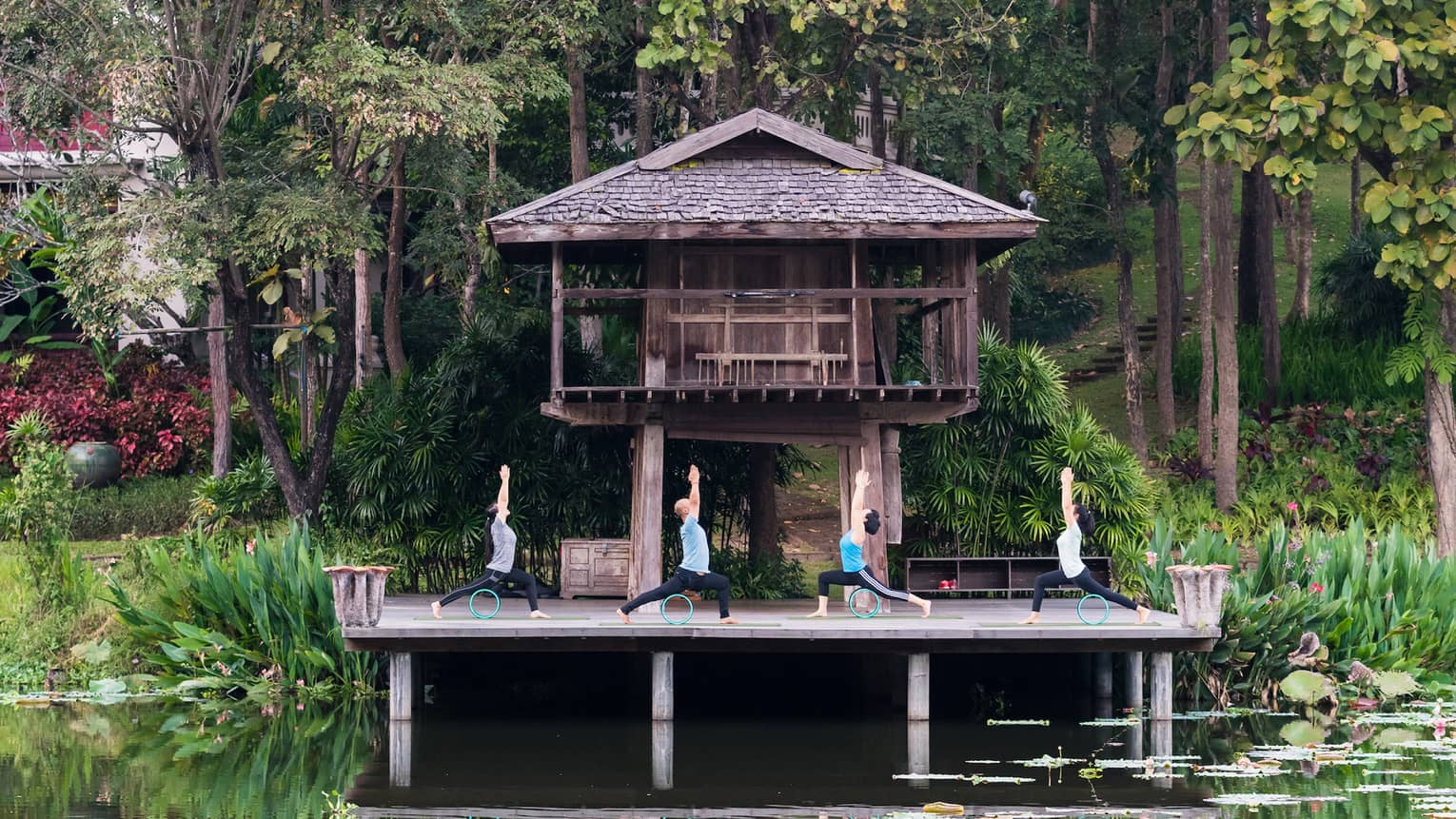 Four people doing yoga on a deck overlooking a calm pond, in front of a wooden bungalow and jungle trees