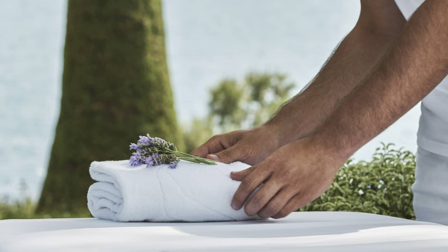 Close-up of hands setting on folded white towel with lavender sprig