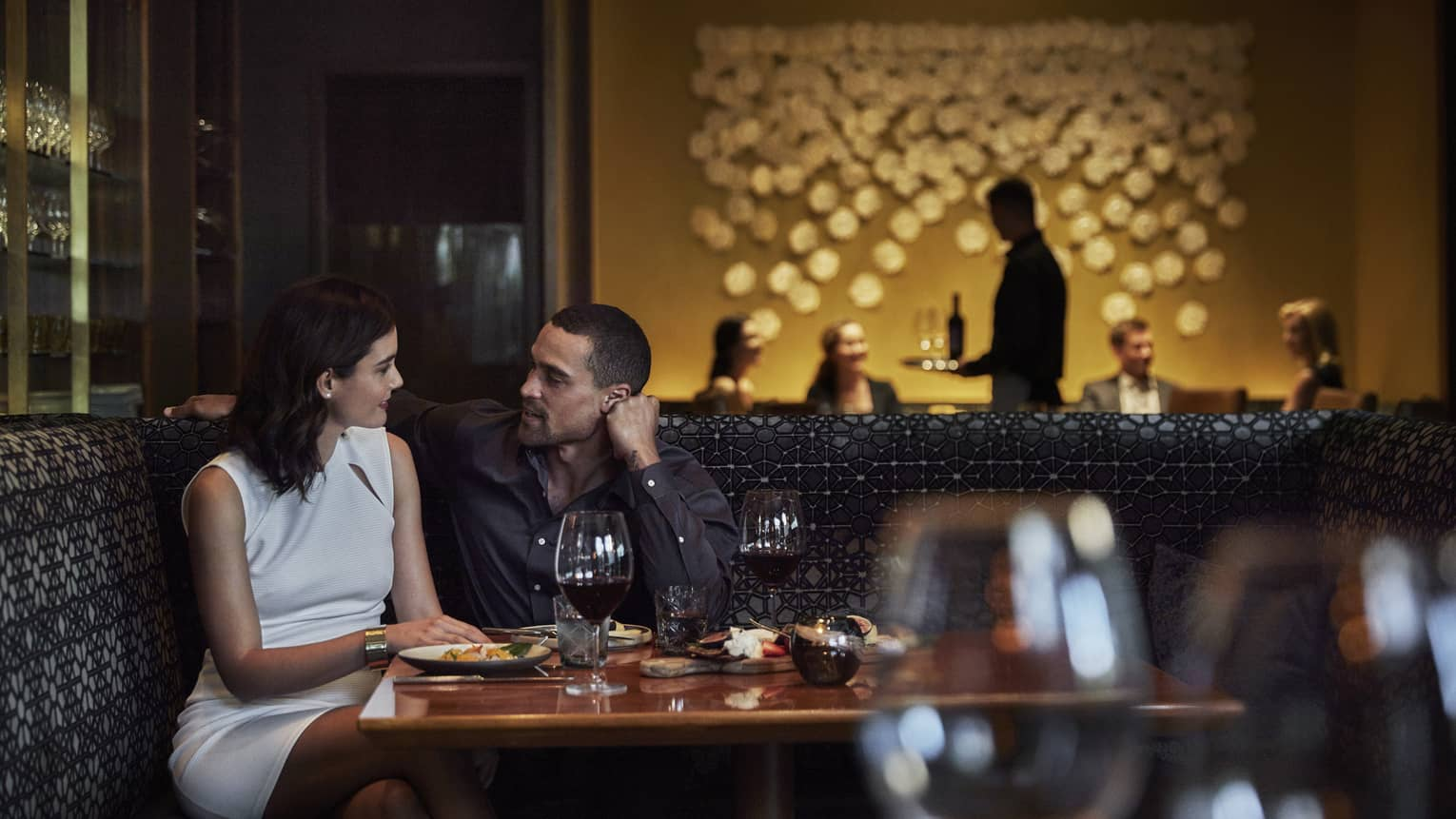 A couple share and dinner and wine in a dimly-lit restaurant, a layered art piece decorates the back wall and empty wine glasses fill the foreground