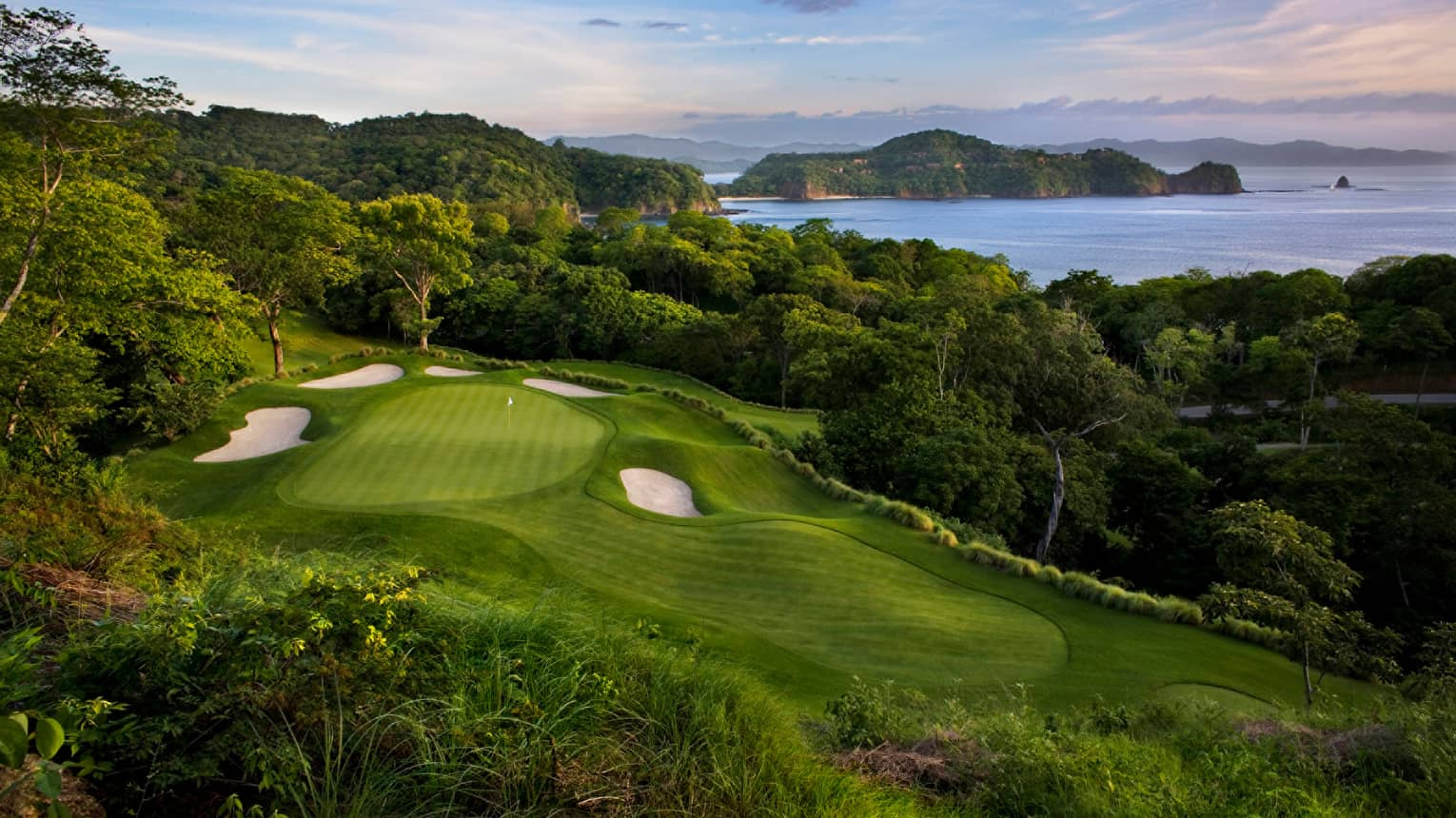 Looking down on golf course green, sand traps on hill overlooking tropical forest, ocean