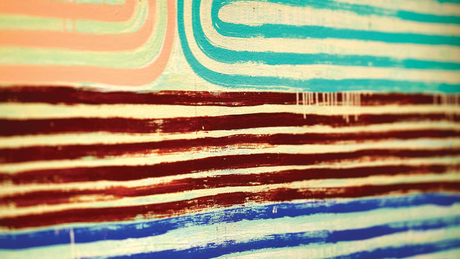 Close-up of pink, teal, red and blue lines of paint in pattern on canvas