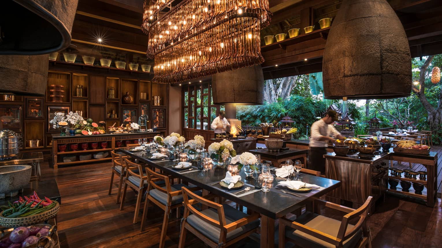 Large dining table under long rectangular crystal chandelier in Rim Tai restaurant, chefs in background