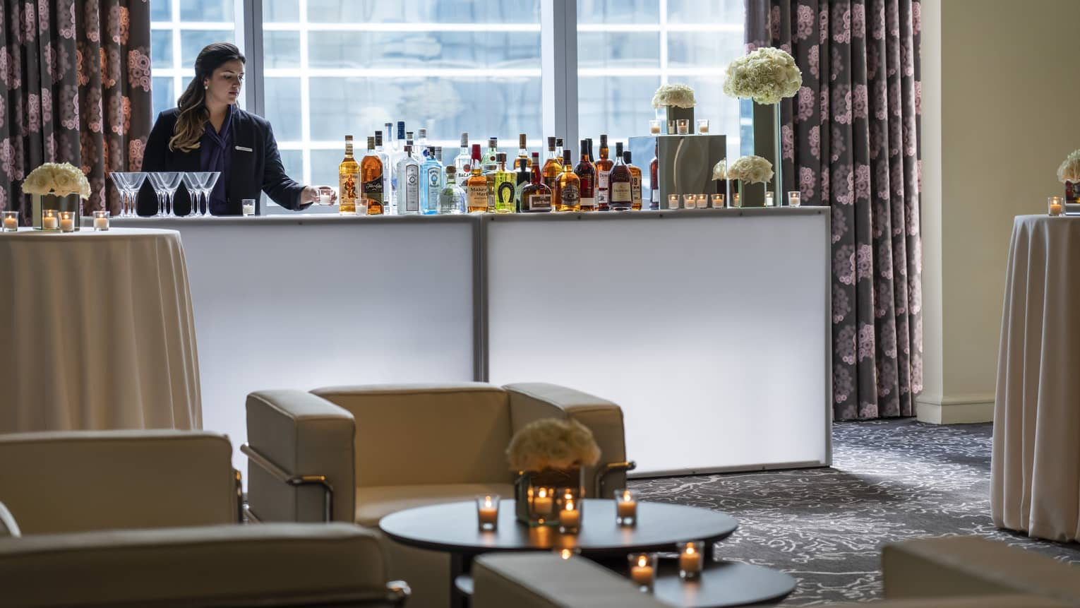 Bartender stands at liquor bottle-lined bar in front of window near seating area