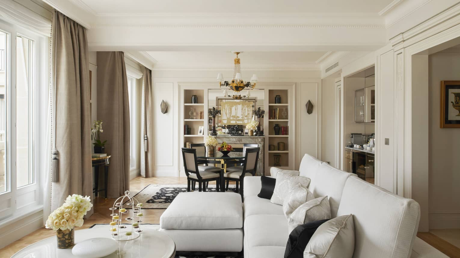 Parisian suite with white couch, coffee table, small table for four, black & white accents