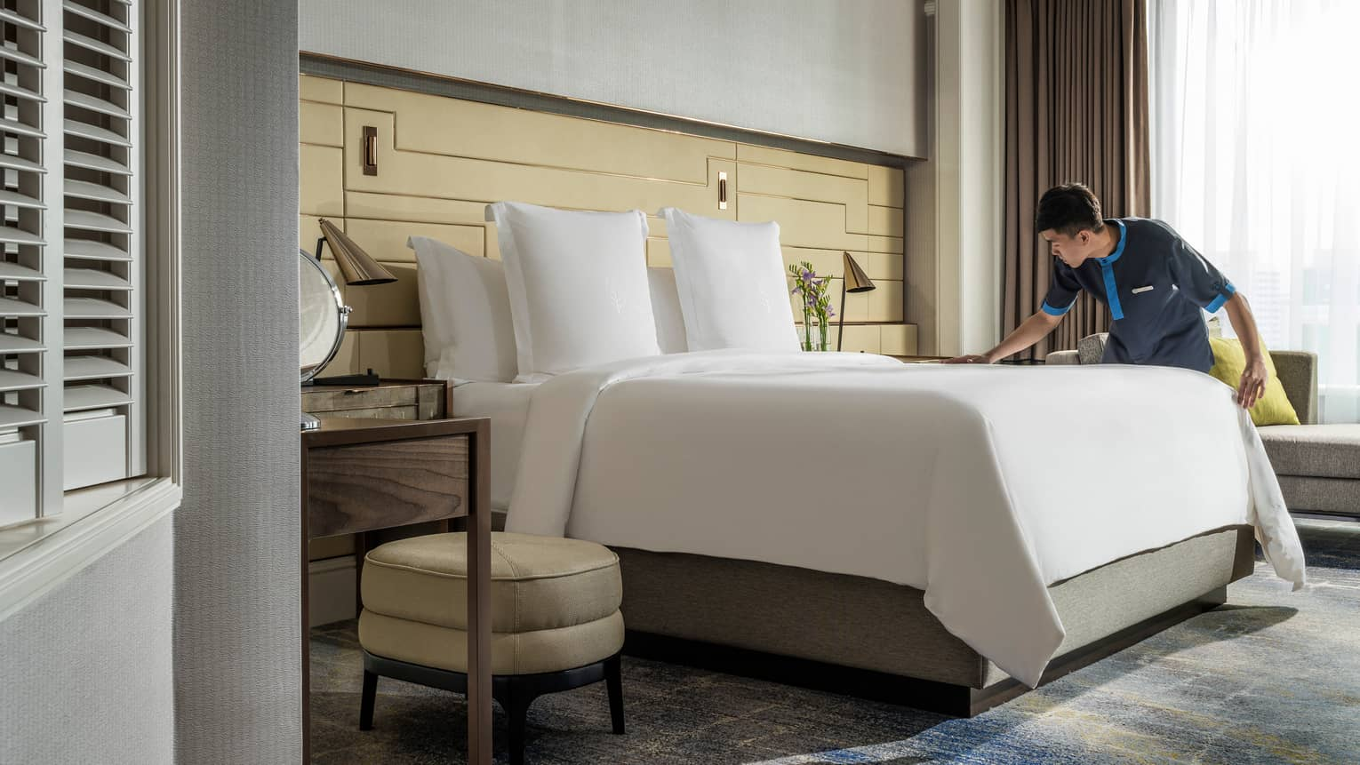 Hotel housekeeper smooths sheet, makes bed in sunny One Bedroom Suite
