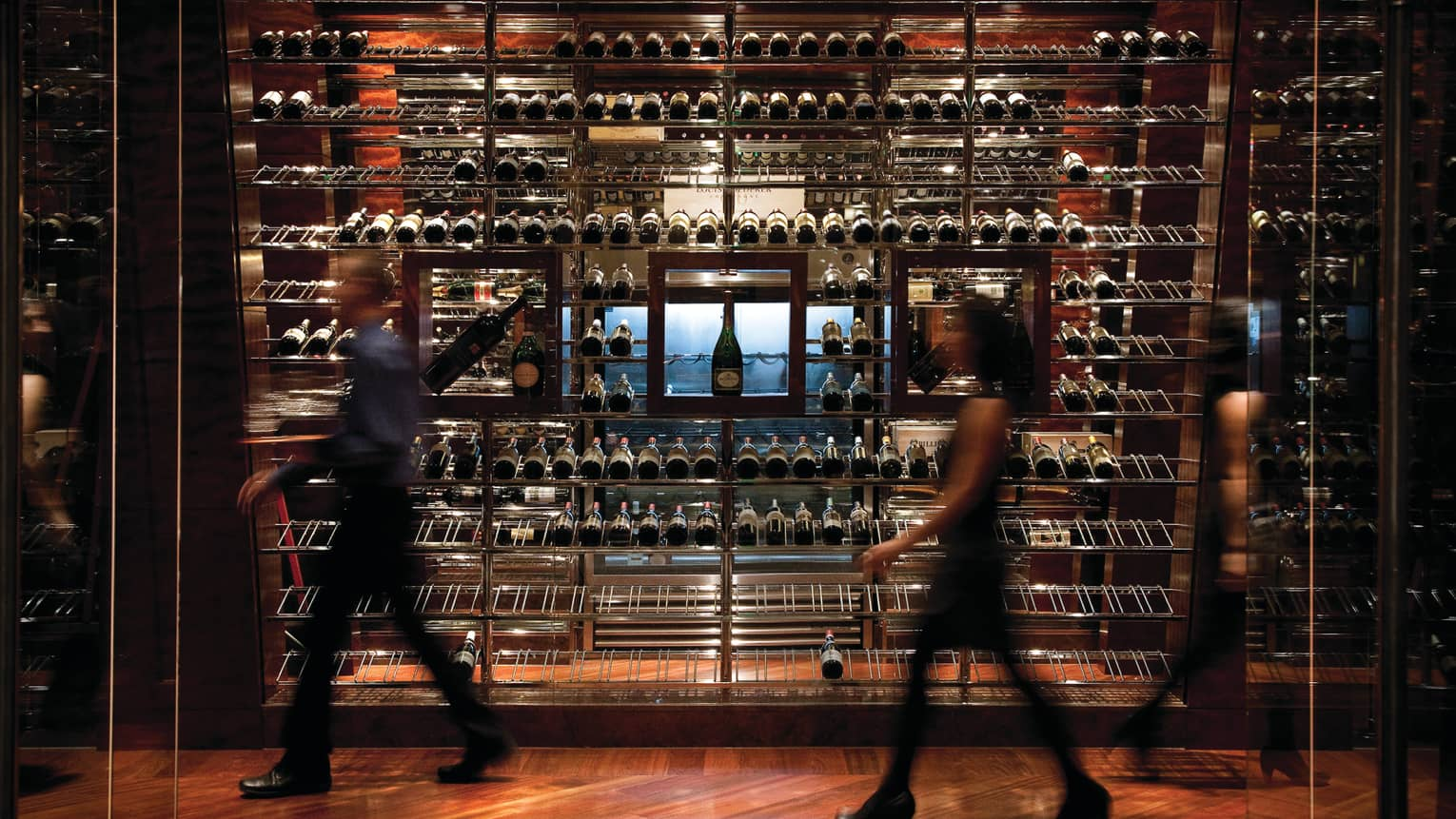 Man and woman walk by dark wine cellar display wall