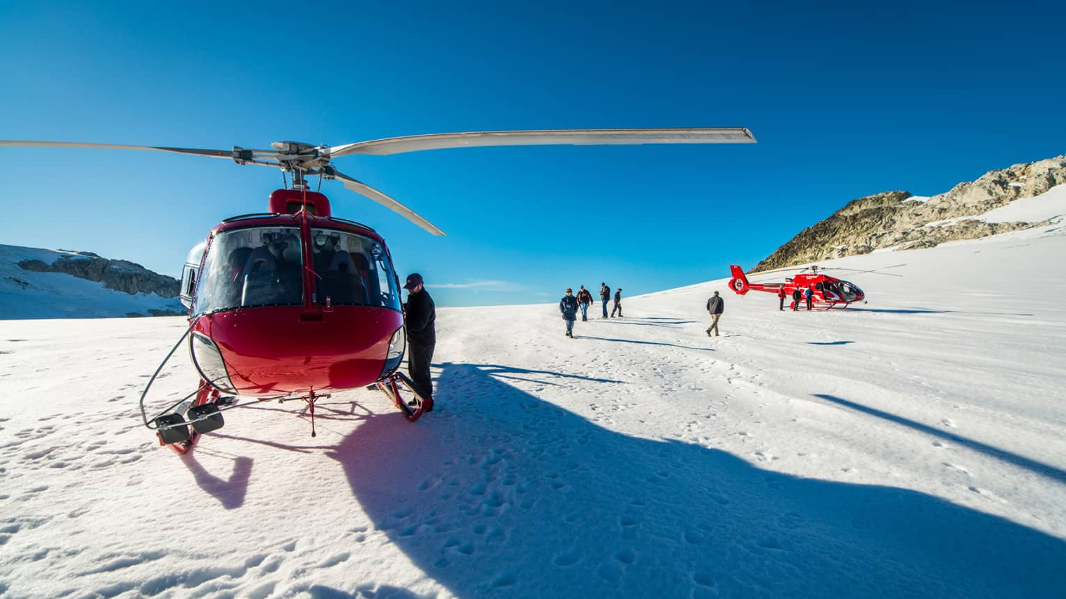 Front view of man getting into red helicopter parked on snowy mountain peak