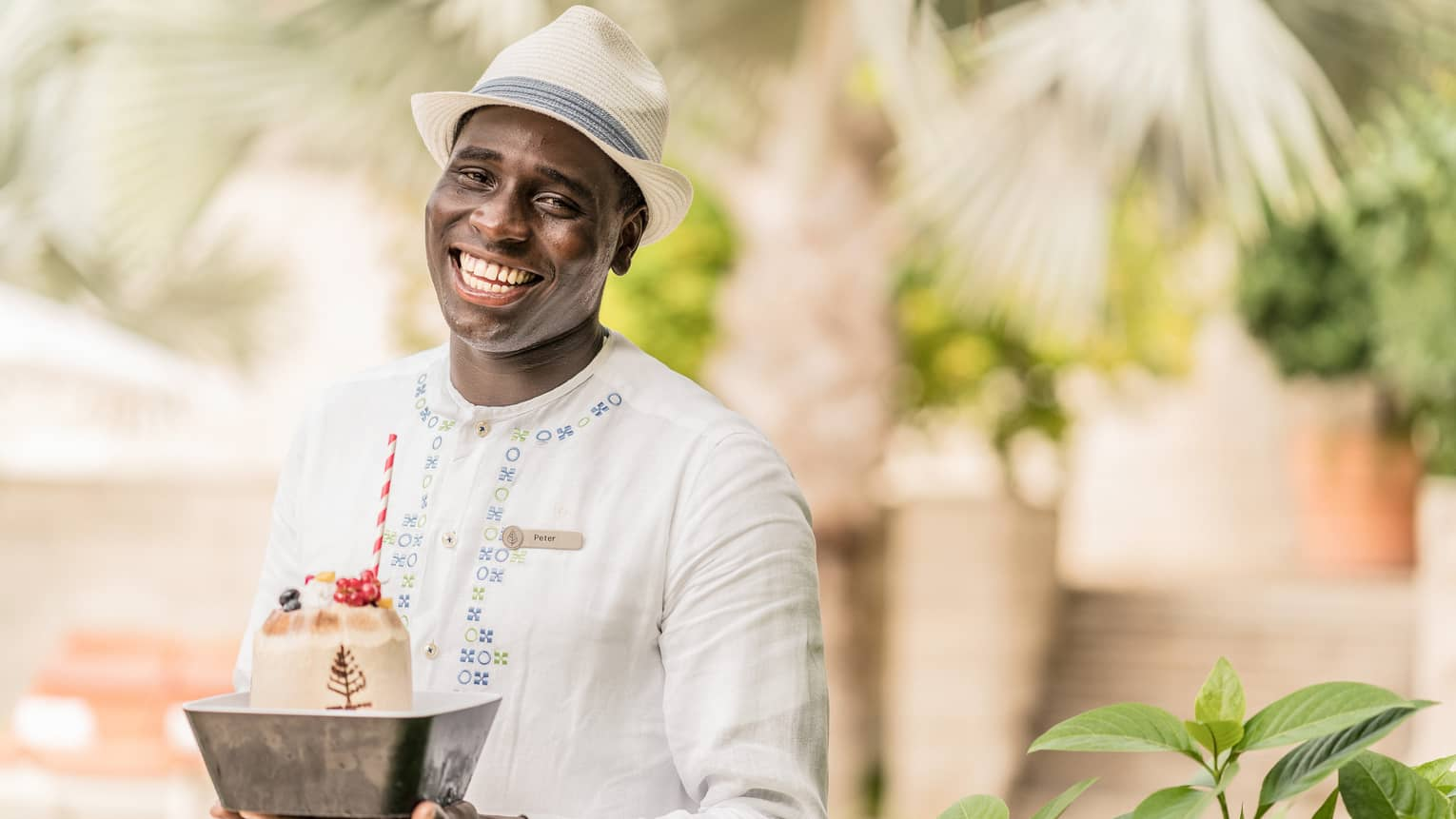 Pool staff member in white tunic and fedora holding ice cream dessert with striped straw