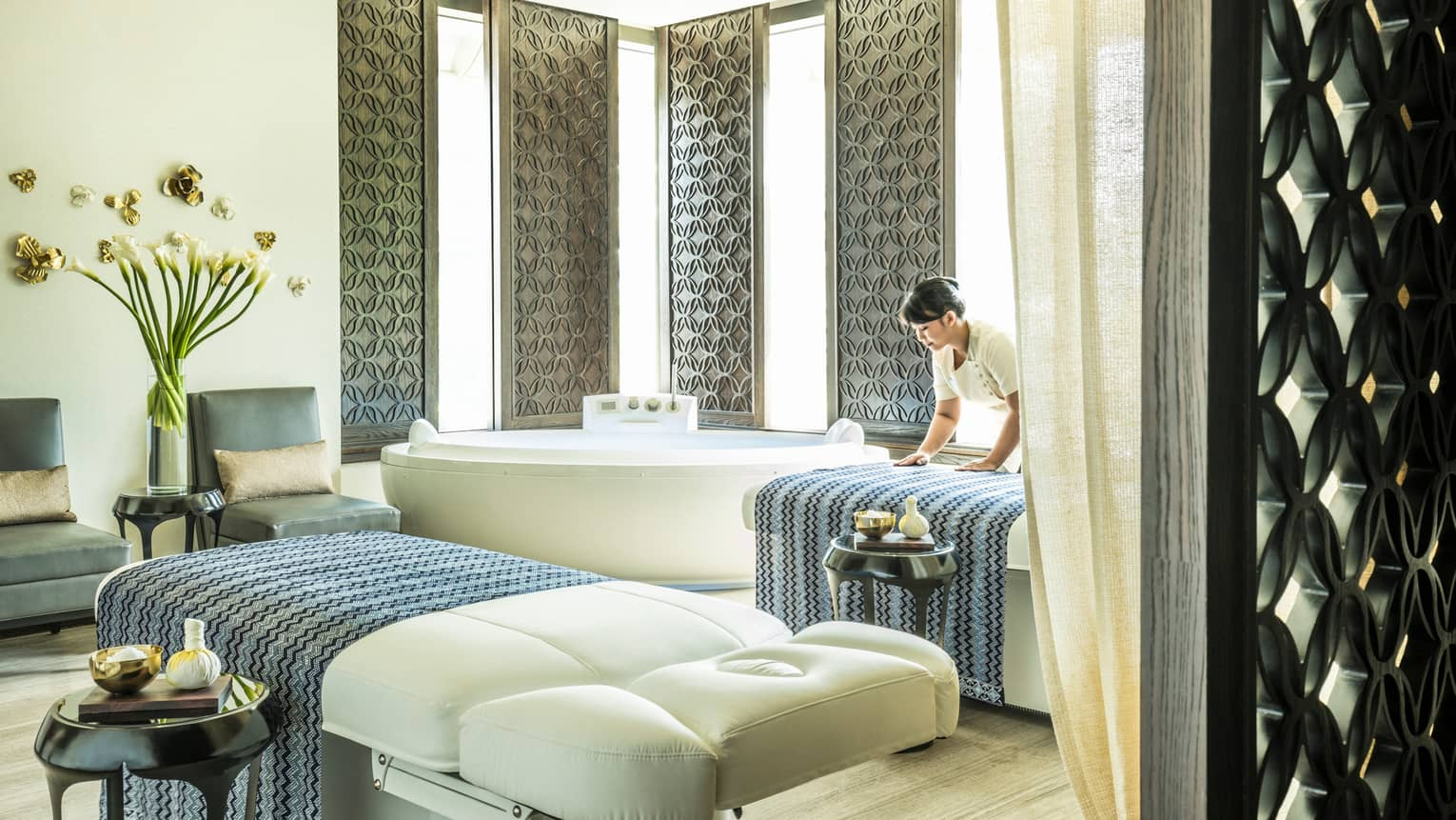 Large white spa table in front of white spa tub, silver wall panels, woman places blanket on table