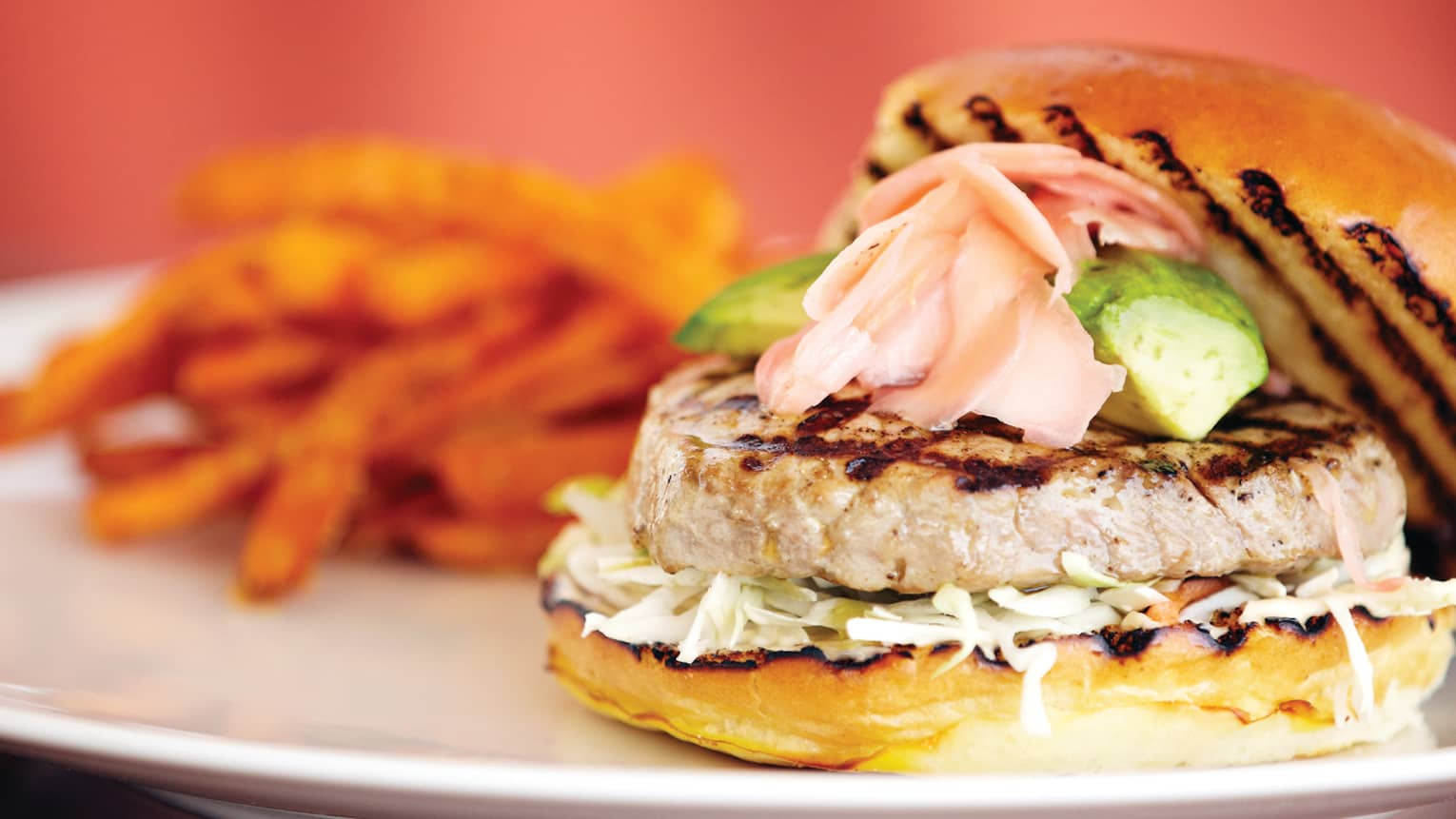 Ahi tuna burger topped with avocado, pickled ginger, side of sweet potato fries