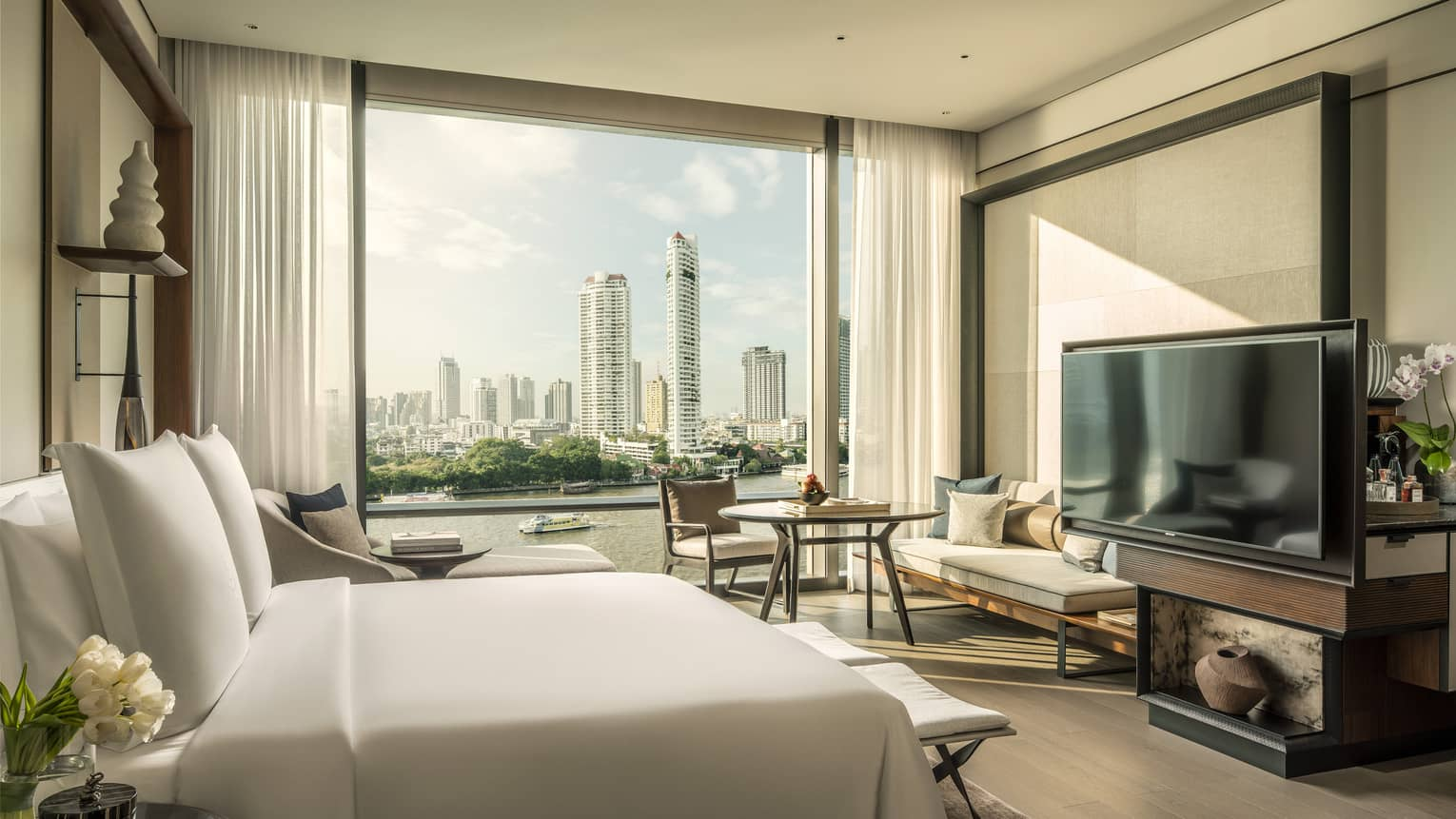 Hotel room with white king bed, view of Chao Phraya River, TV