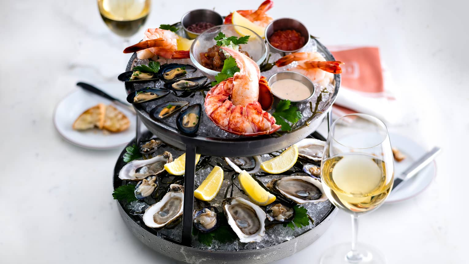 Two-tiered platter with fresh lobsters, oysters, mussels, lemon on ice, glass of white wine