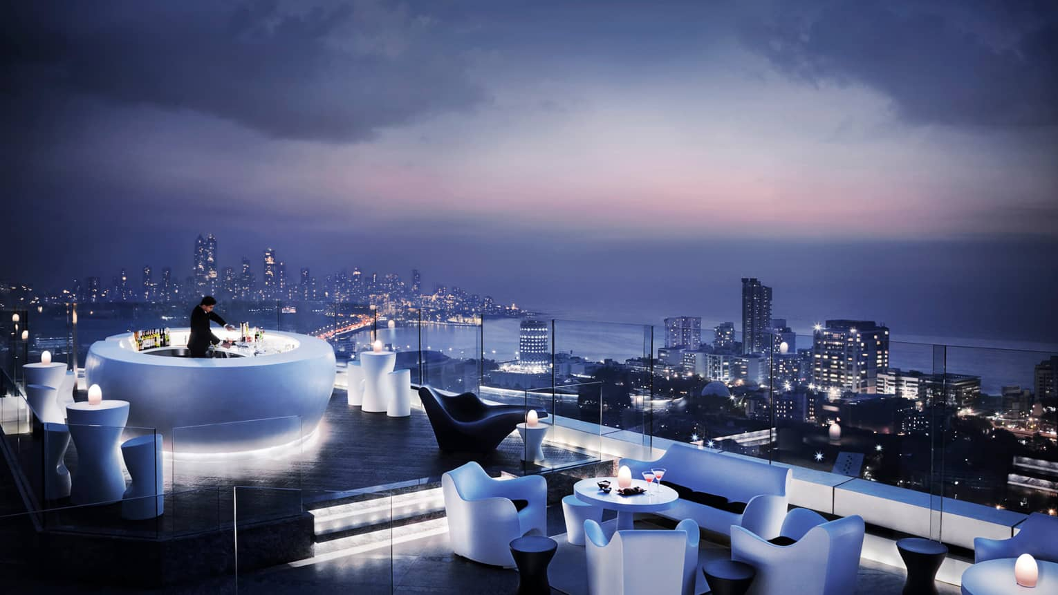 Bartender mixes drink in glowing white circular bar on rooftop lounge, modern chairs and tables