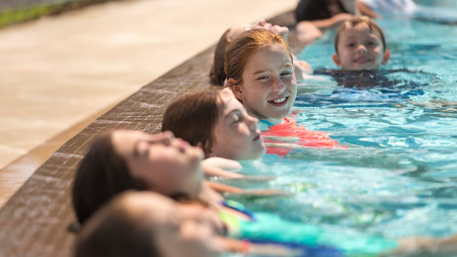 Six children smile, lean their heads against side of swimming pool